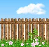 foto of log fence  - Wooden fence on green grass with flowers against the sky - JPG