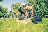 foto of two women taking cell phone  - Couple sitting on grass and taking a selfie after a romantic tour with bicycle  - JPG