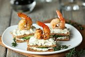 image of canapes  - Appetizer canape with shrimp and cucumber on plate on table close up - JPG