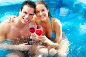 stock photo of hot-tub  - Young couple relaxing in hot tub - JPG