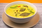 foto of curry chicken  - Hot and spicy chicken green curry on a yellow background on a wood table top - JPG