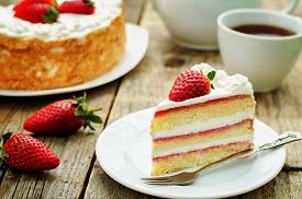 picture of carbohydrate  - cake with cream and strawberries on a dark wood background - JPG