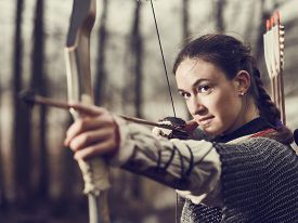 picture of bow arrow  - Medieval archer woman she wearing a chainmail and use a bow and arrow gloomy forest cross - JPG