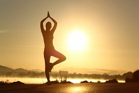 image of breathing exercise  - Silhouette of a fitness woman exercising yoga meditation exercise with the sun in the background - JPG