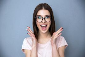 pic of screaming  - Surprised young woman in glasses over gray background - JPG