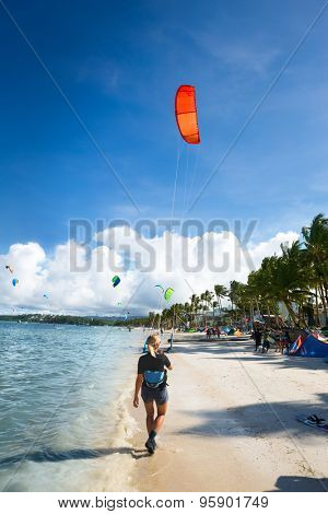 kite surfer preparing for kitesurfing standing on sand on sea cost