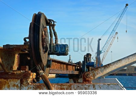 Obsolete Equipment On A Background Of Modern Cranes