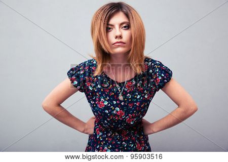 Portrait of angry woman looking at camera over gray background