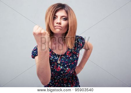 Angry young woman showing fist over gray background