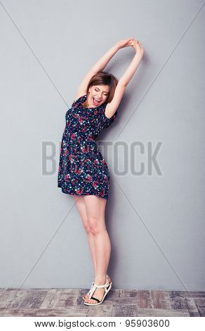 Full length portrait of a young woman in dress yawning and stretching in studio