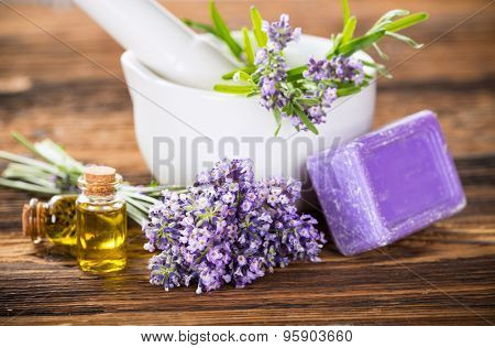 Lavender oil, herbal soap and fresh lavender flowers on wooden background. Wellness still-life.