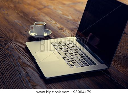 Notebook with cup of coffee on wooden table.