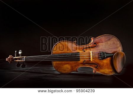 Old vintage violin on black background.