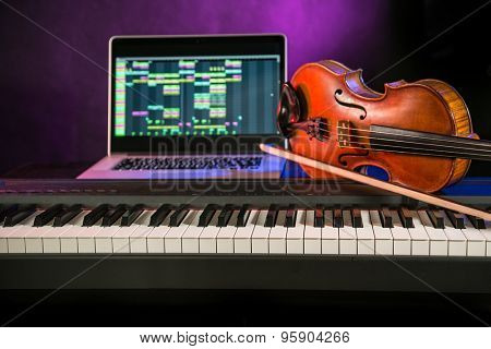 Piano keyboards, old violin and notebook in audio studio.
