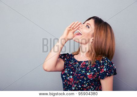 Young woman screaming over gray background. Calling for help