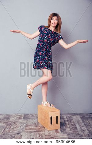 Full length portrait of a funny woman standing on one leg on wooden box