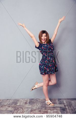 Full length portrait of a cheerful woman standing with hands raised up in studio