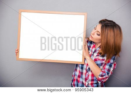 Casual young woman presenting something on a blank board over gray background