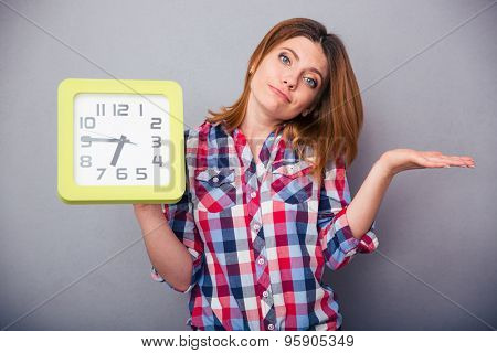 Young casual woman holding clock and shrugging over gray background