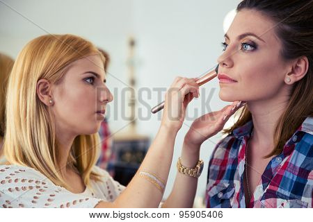 Makeup woman applying makeup to model in salon
