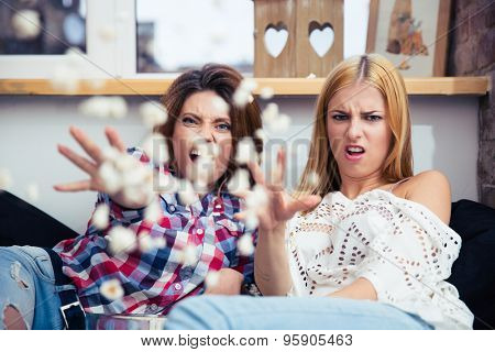 Two young woman sitting on the sofa and throwing popcorn at camera