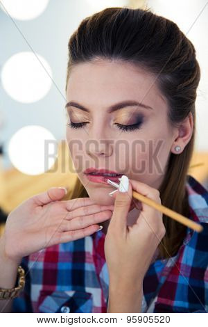 Visagist applying lipstick to woman in beauty salon