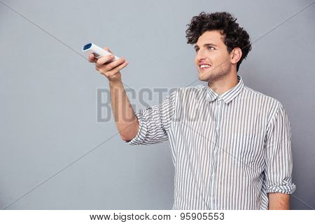 Happy young man holding TV remote over gray background