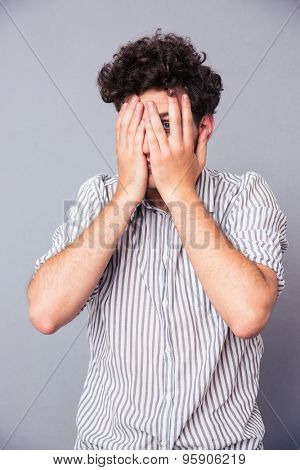 Man covering his eyes and looking at camera through finger over gray background