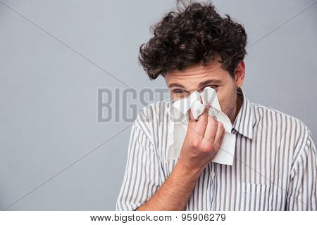 Portrait of a man blowing his nose over gray background
