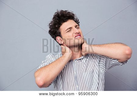 Portrait of a young man having neck ache over gray background