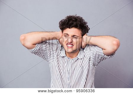 Casual man covering his ears over gray background