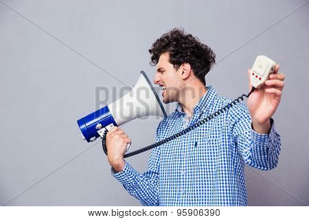 Casual man directing megaphone at herself over gray background