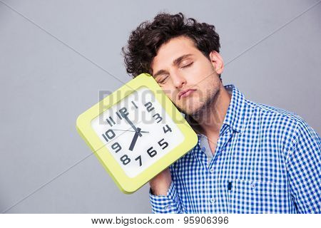 Tired man holding big clock over gray background