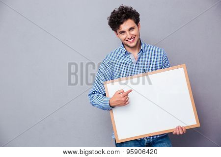 Cheerful man holding blank board and poiting finger on it over gray background and looking at camera