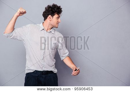 Angry young man with smartphone clenching his fist over gray background