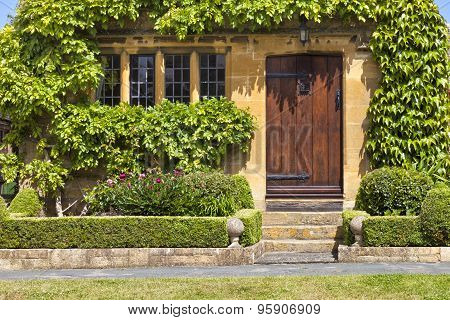 Entrance to traditional English honey golden brown stoned cottage with wooden door surrounded by gre