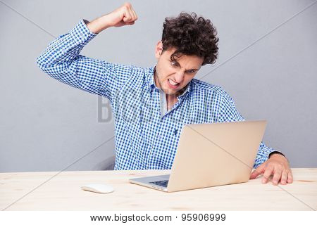 Angry man sitting at the table with laptop over gray background