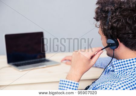 Back view portrait of a male operator with headphones looking at laptop screen