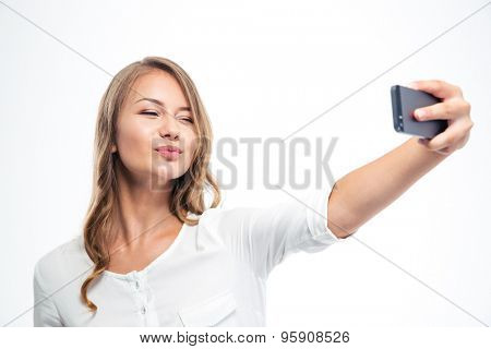 Happy young woman kissing and winking while making selfie photo on smartphone isolated on a white background
