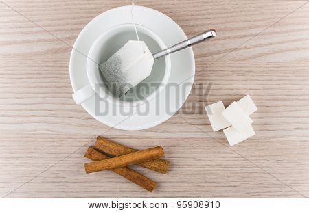 Cup With Tea Bag, Cinnamon Sticks And Pieces Of Sugar