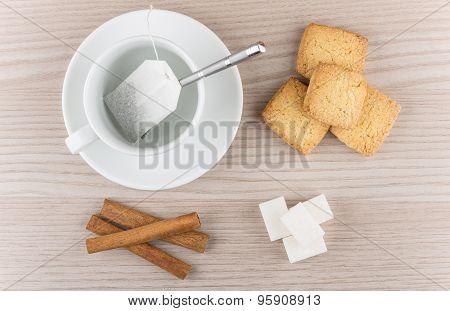 Cup With Tea Bag, Cinnamon Sticks, Shortbread Cookie And Sugar