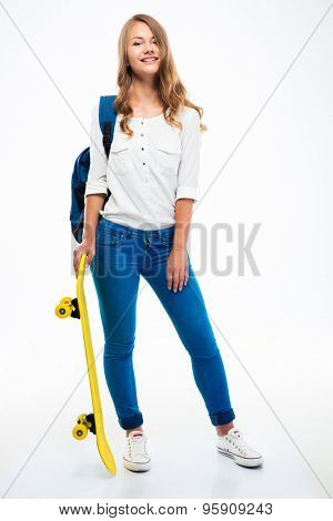 Full length portrait of a young smiling girl with backpack holding skateboard isolated on a white background. Looking at camera