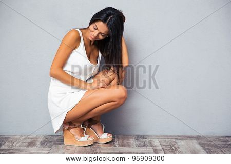 Happy young woman squatting on gray background