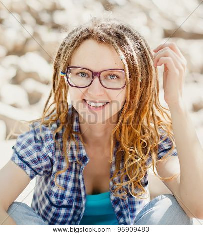 Young cheerful stylish girl with dreadlocks outdoors, close-up.