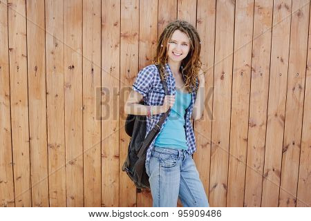 Stylish slim girl with dreadlocks on wooden wall background.