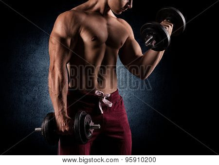 Handsome Power Athletic Man With Dumbbell Confidently Looking Forward.