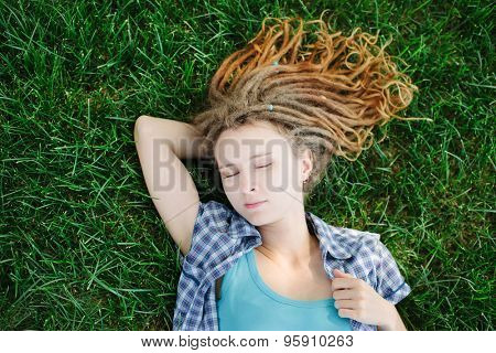 Stylish slim girl with dreadlocks lying on green grass