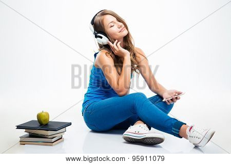 Charming young woman sitting on the floor and listening music on smartphone isolated on a white background