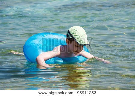 Little boy swimming with inflatable ring
