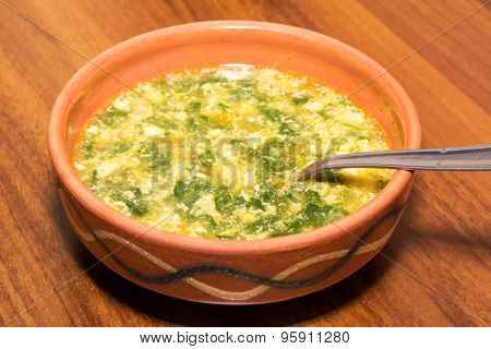 Chard soup in a rustic clay bowl on a wooden table